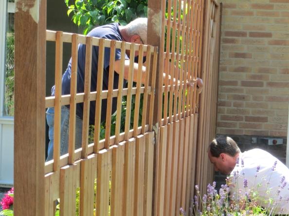 Man Caine en Bert de tuinman werken aan de nieuwe schutting
